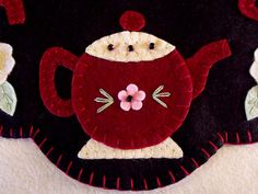 Here I am offering this cute Penny rug - Candlemat featuring 4 burgundy and cream colored teapots with a white flower with a yellow button between each pot. The Tea pot has a pink flower with a black glass bead in the center. Also, across the top of the teapots are 3 more glass beads, stitched securly onto the penny rug. The base and backing are in black and the penny rug is stitched together in the burgundy thread. The penny rug measures 13-1/2 inches in diameter. Such a cute item to…