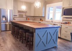 Farmhouse chic: sleek walnut butcher block countertop, barn wood kitchen island, stainless steel appliances.