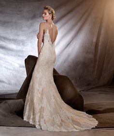 OSERA - Romantic wedding dress that flares out from the hips. This captivating mermaid dress sculpts the body and has a strappy neckline. A wonderful Chantilly dress with lace motifs and gemstone embroidery. An unforgettable jewel of a dress.