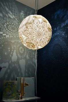 Doiley lamp. Soak doileys in mod podge, place over an inflated balloon(make sure to leave room for the light), give ample time to dry, pop balloon!