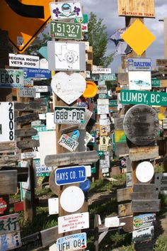 """Signpost Forest, Watson Lake, Yukon.  In this one are: A picture of george Washington, """"BEACH"""", purple irises, an owl, an eagle, and some red flowers.  06/2013."""
