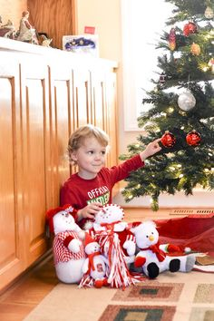 official mistletoe tester son smile smiles laugh candid happy Christmas family card post pose poses photo photos picture pictures portrait portraits son boy happy GloryRoze Photography december photoshoot shoots fence child indoor christmas tree family of four two sons boys children mom dad mother father candid candids smiles laughter laughing laugh smile happy sneaky ornaments