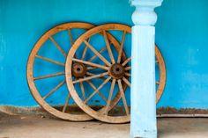 Wagon wheels against blue wall in rural village.