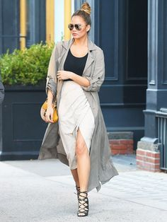 Chrissy Teigen wears a black top, wrap skirt, long duster jacket, and lace-up heels with a Chloé Drew bag and aviator sunglasses