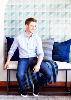 Ben McKenzie against blue home décor... Great mix of ethnic feeling textiles, warm woods and leather plus clean lines