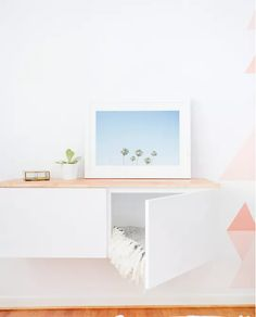 Cabinets offer plenty of storage, but can look bulky (and consume precious square footage). Enter: A floating system. Here, a white IKEA piece nearly blends into the white wall it's mounted on so it appears less clunky. It's especially great in a living room, where you can toss your pillows and throws into it when not in use.