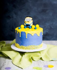 Minion Drip Cake - keep the kids entertained with a delicious Minions Drip Cake coming in your favourite Minions colours. This drip cake is decorated with a blue cream and a yellow icing ganache dripping down the side