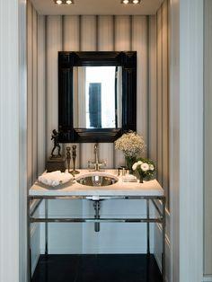 Un mueble de acero con encimera de mármol, un espejo con marco negro, papel de rayas en la pared y zócalo en la zona inferior