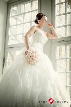 Gorgeous Shot of Bride looking out the window as she awaits her groom. Photo by Zana Photos