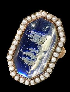 Man's ring dating to ca.1798-1800. Seed pearls surround etched cobalt blue glass. The micro carving depicts the Battle of St. Vincent in 1797.
