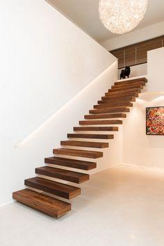 Moderne zwevende trap met wit gelakte muurgreep in metaal en LED verlichting