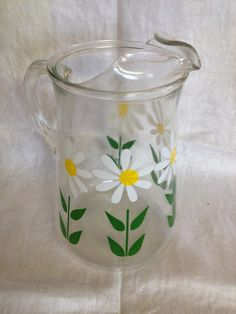 Vintage glass juice pitcher with daisies. No chips or cracks. Measures 4 1/2 diameter at the top, 5 1/2 diameter at the bottom. 9 tall  ENTER