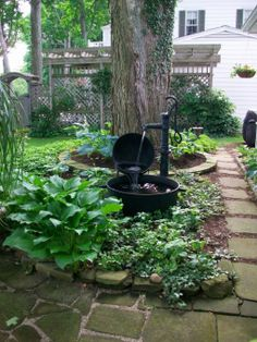 Homemade fountain: created from a cast iron scalding pot, a cauldron, and a hand pump w/ original insides removed. Rubber tube run through pump. The falling water covers the tube and wire for the submersible pump that is in the largest pot.