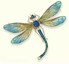 AN EARLY 20TH CENTURY ENAMEL AND GEM-SET BROOCH. Modelled as a dragonfly, the plique-à-jour enamel wings with rose-cut diamond line detail to the sapphire collet body, diamond and ruby head and blue and green enamel abdomen, mounted in gold, detachable brooch and hairpin fitting, circa 1900, 6.8 cm wide, in brown leather fitted case