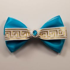 Princess Jasmine Inspired Bow This bow, inspired by Princess Jasmine, is a bright teal blue just like Jasmine's outfit and has accents of gold patterned ribbon. It also features a blue gem widget on the front similar to Jasmine's jewelry. This bow is approximately 5 inches wide. Featuring a french barrette, this bow can be worn however you like in your hair.  Perfect for a day at the Disney Theme Parks!