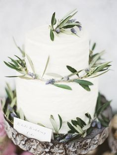 white cake on wood platterwith accents of herbs and berries, photo by Erich McVey Photography