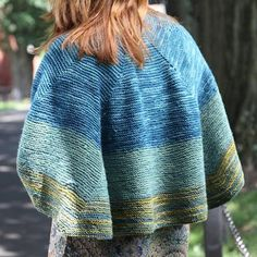The Foxfire Shawl has increasingly longer rows that cause the color blocks to shorten in a natural progression while the graceful shape hugs your shoulders. Beautiful blues and greens knit in Valley Yarns Charlemont Kettle Dye and Hand Dye yarn.