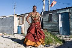 British Photographer, Araminta de Clermont, has a series of photos of women in their matric farewell dresses. They pose in front of their homes, all of whom hail from the Cape Flats area. This is Nomhla from Khayelitsha. I love her dress, it is so ethnic and traditional!