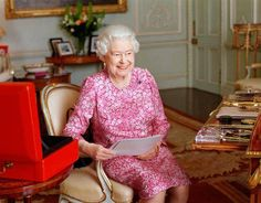 The Queen seated at her desk in her private audience room at Buckingham Palace with one of her official red boxes
