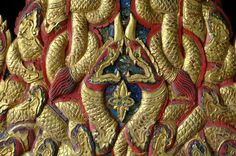 One sees four Nagas on each side with the center two coming together. In their mouths they hold the image of a precious gem, created by foil backed glass inlay. Highly symmetrical, this piece showcases seven candle holders whose light could remind us of the protection provided the Buddha by the Nagas.  With fiercely upturned mouths, the Nagas are a form of celestial serpent or dragon who have come into the service of the Buddha. They are often seen in the form of the King Cobra wherein the…