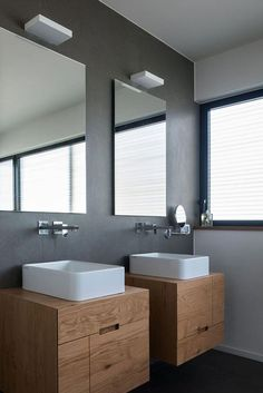 In this bathroom, grey walls and floors have been combined with a white sinks and two wall-mounted wood vanities to create a modern look. Grey Bathrooms, Modern Bathroom, Small Bathroom, Bathroom Sink Cabinets, Bathroom Furniture, New Modern House, Dark Brown Cabinets, Bathroom Wall Lights, White Sink