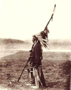 UNIDENTIFIED MAN OUTDOORS—The head dress is made of golden eagle feathers and has a beaded head band trimmed with ermine fur.  The lance (pointed down), wrapped with cloth, is decorated with feathers and cloth. Around his waist is, apparently, a set of harness sleigh bells.  No date.   6¼  x  8¼ inch mounted on 11x14 inch archive rag board.