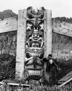 Pole sits amid the grasses at Skidegate, exerting its authority as an anchoring presence. It speaks of belonging, and is materially of a piece with its natural surroundings. | Royal BC Museum and Archives