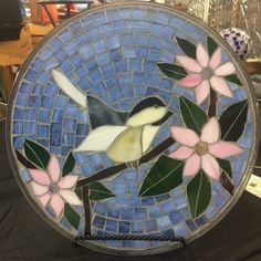 Mosaic display plate created with stained glass and grout. Base is recycled 12 microwave plate.  The design is a happy chickadee sitting on a flowering tree branch. Glass colors used include light blue, black, gray, beige, pink, green, brown and purple. The grout color is light gray.  Stand included. Indoor display only. Wipe clean with old t-shirt or lint free cloth taking care to avoid possible sharp edges.