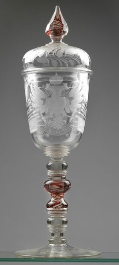 """Lidded goblet with inscription """"Leopold I. G. Rom. Imp. S. A. Ge. Hu. Bo. Rex"""",  Glass, colourless, conical cup decorated with medallion containing the cut portrait and around it the inscription, flanked by flags and instruments of war, to the reverse the Habsburg eagle, finial and shaft with red spiral trail, lid with cut border of foliage and blossom pattern, smooth base with pontil mark, height 41 cm, finial end minimally chipped, Bohemia around 1760"""