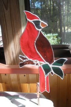 This Cardinal is designed and made by me to sit on a garden stake in the summer months and dress up your window sill or table in the winter months. This stained glass cardinal is 8 1/2 tall and 5 wide, made with glass, copper foil and solder. It also has a simple wood (cedar) base for indoor décor. The garden stake itself can be purchased at your local hardware store for less then I can ship it. Just a 3/16 dia. rod will do it.  These are fun and unique.