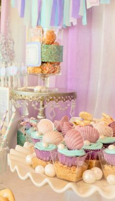 purple foil lined cupcakes topped with purple chocolate shells and gumball pearls, set in cups of graham cracker sand