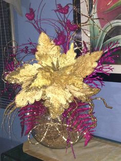 A really big gold flower with some color accents floating on top of a crystal round vase makes a statement.