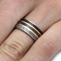 For him: This wedding ring features a trio of rare materials, Gibeon Meteorite. Petrified Wood, and Fossil.