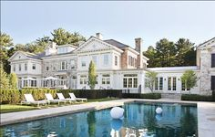 An All White South Hampton Mansion With Black Shutters On A Beautiful
