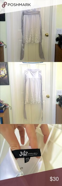 Beautiful White and Silver Dress Pure white with silver sash and confetti.  Polyester dress with a satin look. Spaghetti straps and zipper in the back. Worn once, practically new. Falls to mid-thigh, approximately. Would look lovely with silver strapped shoes for a formal occasion. Jump Dresses Midi