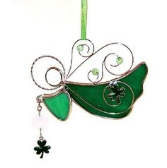 """Irish Angel Stained Glass Suncatcher. A whimsical addition to any Irish collection. This angel holds a shamrock and is accented with green beads. Measures 3.5"""" x 4"""". Comes with a ribbon for hanging in"""