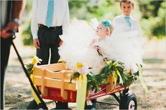 If your flower girl is a bit too young to proceed alone, here's a great way to get her down the aisle at an outdoor wedding. #flower girls/ring bearers
