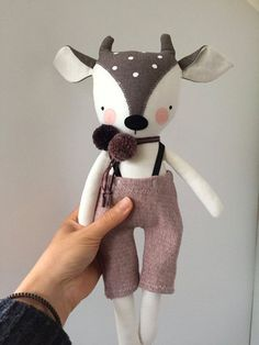 Luckyjuju dolls are handmade from mostly new, but sometimes vintage or upcycled fabrics, yarn, and 100% wool felt. The face has hand draw, hand painted and hand embroidered elements. They are made to be played with and loved by gentle children over 3. This fawn comes with pompoms and red and white pinstriped pants. His clothing is designed to be removable, but please keep in mind that some of the fabrics may be delicate and should be taken on and off with care. ***Children under 3 should not…