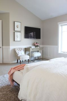 Gorgeous bedroom features beige paint on upper walls and wainscoting on lower walls framing flatscreen TV over curved gray console table next to stacked art above beige tufted chair. A queen bed is dressed in soft white bedding as well as striped sofa placed at the foot of the bed.