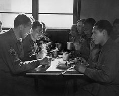 African American, Chinese, Puerto Rican, and White US soldiers eating together in a mess hall. They are all serving at the Army Quartermaster Supply Depot in England. 1944.