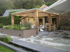 Glass roofed pergolas with laser cut stainless steel braces, a built in fireplace and chimney made by us from Corten steel, and log stores.