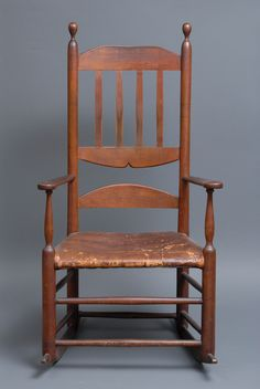UNIQUE SHAKER ROCKING CHAIR  Birch, original brown stained finish with exceptional patina, Alfred, ME, c. 1820, from the scribe lines on the back posts, the chair was originally designed to have four slats, however, the maker decided to combine the form of a worldly bannister back and the Shaker ladderback with four half-round vertical pieces fitted into a top slat and in the upside down carved slat on the bottom with an arched Shaker style ladder below, flattened and beveled scrolled arms…