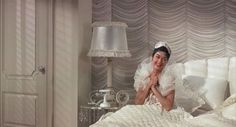 """Auntie Mame wakes up feeling a little """"hung"""" while still looking beautiful in her white and pink bedroom"""