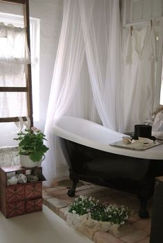 Clawfoot tub. Bricks. Plants. Shower curtain. LOVE it all
