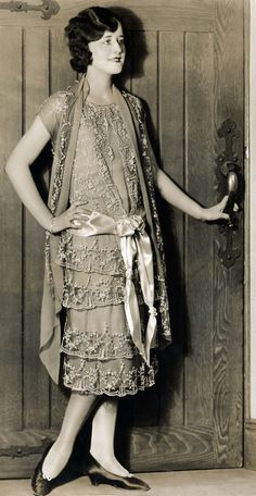 Women's Fashion. Young woman shows one example of the spring fashion 1925. A loose gown with 'jacket'. The dress has a tulle - and low side and around the waist is a great bow of silk draped. [Paris], France, 1925.