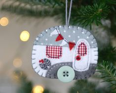 Grey and white vintage caravan Christmas ornament. This vintage caravan trailer ornament is handmade from felt and decorated with fabric scraps. With tiny felt bunting and buttons for the wheel and…