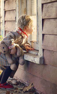 Little girl with teddy bear peeking in a window - makes me smile!
