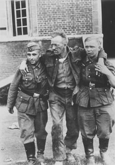 Two German soldiers are helping a wounded Canadian prisoner in the street of the French city of Dieppe.