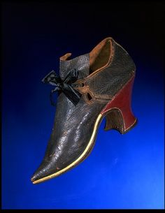 Pair of shoes, England, Britain (made)  ca. 1700, Materials: Leather with vellum rand; modern ribbon added for latchet fastening. These elegant women's shoes are made of plain leather. This is rather unusual, as shoemakers more commonly used plain leather for working women's shoes. The red leather heel contrasts with the dark upper. From 1675-1700 shoemakers used pointed toes for women's shoes only. This was the first major difference between fashionable footwear for men and women.