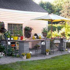 fabriquez un coin bar dans le jardin avec des pieds en parpaings scellés  dans le sol et recouverts d'un comptoir en bois exotique. Pour l'entretien, juste une huile pour teck sur le plateau une fois par an.